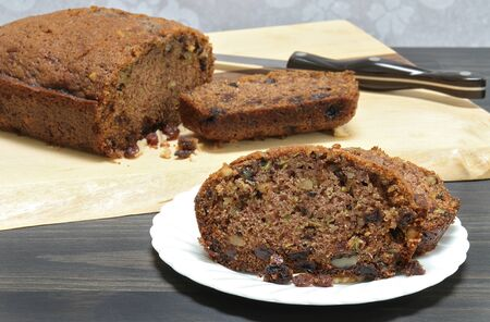 Slices and a partial loaf of homemade zucchini bread with walnuts and raisins.  Close up with selective focus on slices.