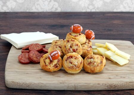 Party snacks of sliced pepperoni, cheddar cheese and pepperoni pinwheels.  Decorated with footballs, great snacks for the Super Bowl or a masculime celebration. Copy space.
