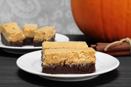 Pumpkin cheesecake brownie bars.  Great addition to the holiday table for Thanksgiving or a Halloween celebration. Stock Photo