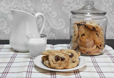 Chocolate chip cookies on a plate and a gass of milk  in front of a glass cookie jar. Stok Fotoğraf