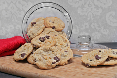 Chocolate chip and walnut cookies spilling out of a glass cookie jar. Stok Fotoğraf