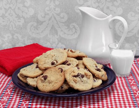 A large plate of homemade chocolate chip and walnut cookies with a pitcher and a glass of milk.