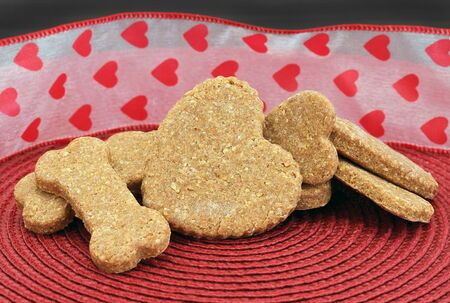 A stack of homemade dog biscuits, bone and heart shaped, in front of a festive Valentines Day ribbon. Stok Fotoğraf