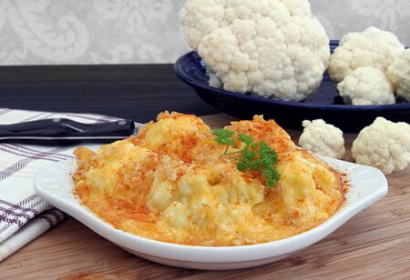 A casserole of baked cauliflower in a creamy cheddar cheese sauce, garnished with paprika and fresh parsley. Stok Fotoğraf