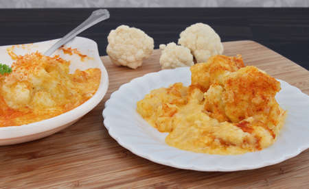 A serving of creamy cheddar cheese cauliflower casserole, garnished with paprika.