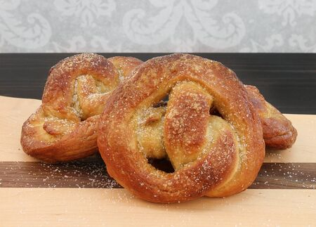 A stack of salted homemade soft pretzels on a cutting board.