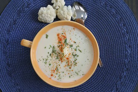 A bowl of healthy cream of cauliflower soup, top view, garnished.
