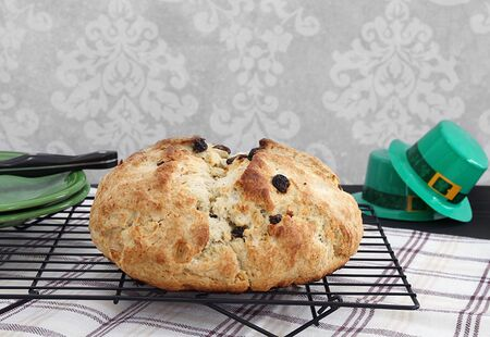 Homemade, freshly baked Irish Soda Bread on a cooling rack.  Irish decorations to the side.  Great for St. Patricks Day celebration. Stok Fotoğraf