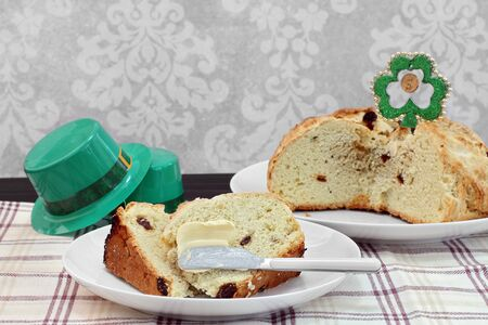 Slices of Irish Soda Bread on a plate being buttered with the whole cake in the background.  St. Patrick Day Celebration decorations.