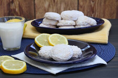 Table setting of fresh lemon cookies, lemon slices, and a glass of milk.  Three cookies in front with a full platter in the background.Close up.