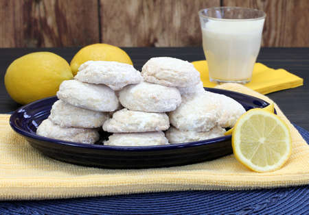 A blue plate stacked with sugared lemon cookies with lemons and milk. Stok Fotoğraf