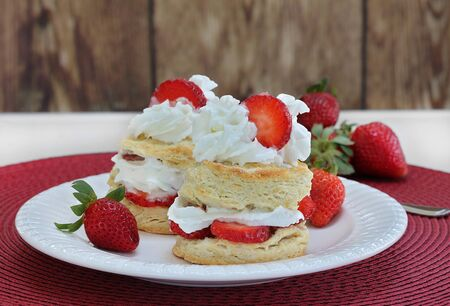 Two delicious strawberry shortcakes with whipped cream and garnished with a sliced berry.  Dessert  on a white plate with additional strawberries.  Close up with copy space. Stok Fotoğraf