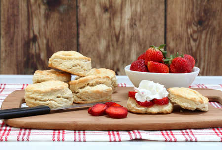 Ingredients for making strawberry shortcake to include strawberries, buttermilk, biscuits and whipped cream.  Front view with copy space.