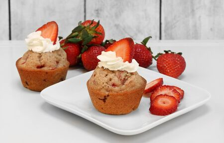 Two fresh baked strawberry muffins topped with fresh whipped cream with a berry slice. Stok Fotoğraf