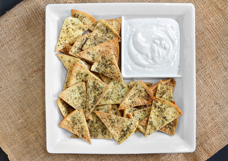Top view of homemade spicy pita chips with dip.  Chips and dip are in a white chip dish. Stok Fotoğraf