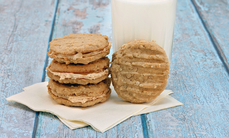 A stack of filled peanut butter and oatmeal cookies with one leaning on a glass of milk.  Blue rustic table.  Copy space. Stok Fotoğraf