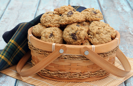 Homemade oatmeal raisin cookies in a basket on a blue rustic table. Stok Fotoğraf