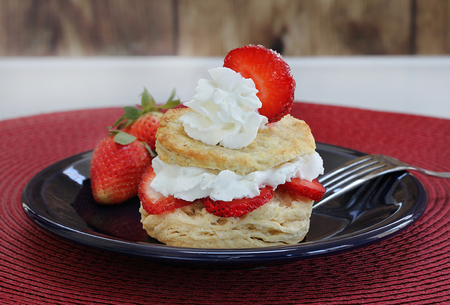 Fresh and healthy homemade strawberry shortcake with whipped cream and fresh berries and garnished with a strawberry slice.  Macro with copy space. Stock Photo