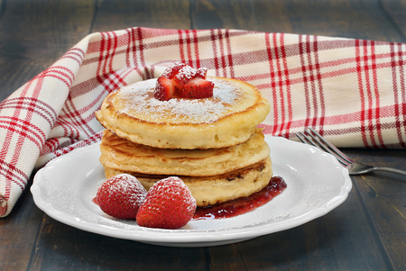 Three homemade pancakes with fresh strawberries and powdered sugar.  On a vintage wooden table with a red and white towel swirled behind plate.