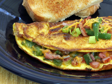 An extreme macro of a Western or Denver omelet.  Omelet includes ham, cheese, peppers, and onions.