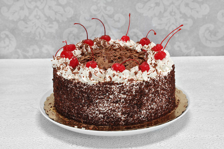 Beautiful black forest chocolate cake complete with cherries and whipped cream on a white lace tablecloth.   Macro with copy space.