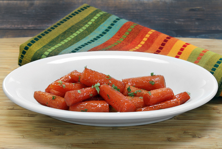 A bowl of fresh, organic carrots roasted in honey and butter.  Close up.