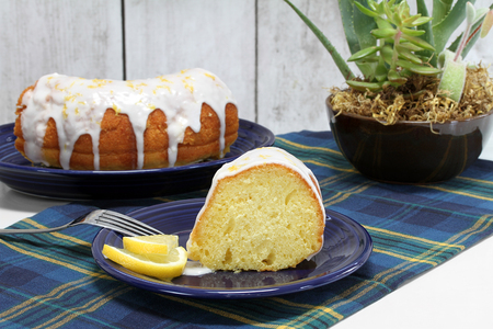 A slice of lemon bundt pound cake with white icing.  Cut cake in background.