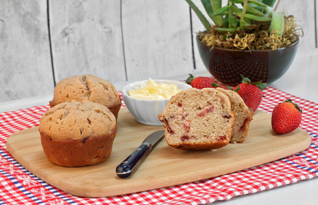 Homemade organic strawberry muffins, whole and cut, with fresh strawberries on a cutting board.  A bowl of whipped butter to the side.Close up with copy space.