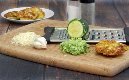 Preparing zucchini squash fritters on a cutting board with zucchini, garlic, spices, grated cheese and a grater. Stockfoto
