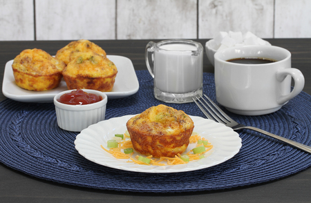 Egg, bacon and cheddar breakfast muffins on a table setting including coffee.  Close up.