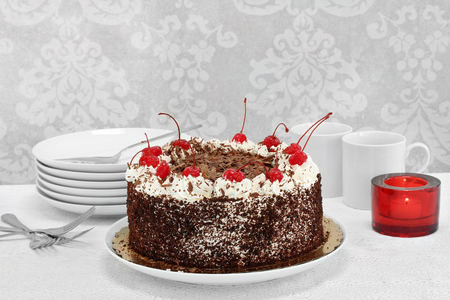 One whole German black forest cake with cherries and whipped cream.  Table setting with plates, cups and a lit candle.