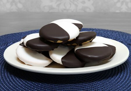 Black and white cookies stacked on an oval plate.  Macro, close up with copy space. Stok Fotoğraf