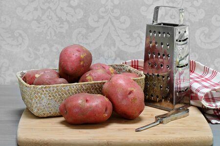 Pommes de terre rouges biologiques crues dans un panier. Le panier est sur une planche à découper avec éplucheur et déchiqueteuse.