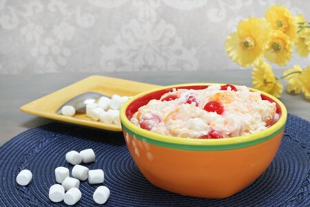 A colorful bowl of ambrosia salad made with marshmallows, oranges, pineapple, cherries, sour cream and coconut  Macro with selective focus on center cherry and copy space. Stok Fotoğraf