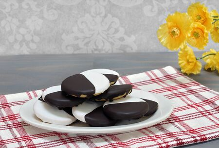 Black and White cookies stacked on an oval white platter.  Close up with copy space.
