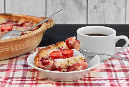 One serving of fresh strawberry cobbler with fork holding portion.  Full dish and cup of coffee included.
