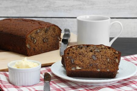 A serving of banana lnut bread with butter and coffee to the side.  Close up macro. Archivio Fotografico