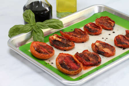 Roasted plum tomatoes with olive oil, balsamic vinegar, spices and basil on a baking sheet. Macro with selective focus on front tomatoes. Archivio Fotografico