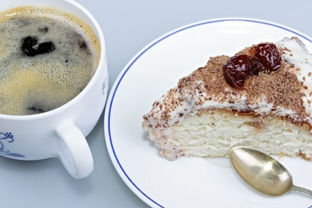 piped: Cake on a plate with a cup of coffee.