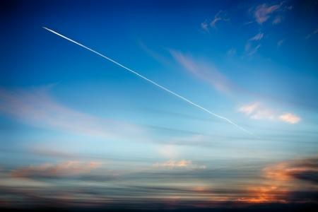 plan éloigné: Suivre avion dans le ciel sur le fond d'un beau coucher de soleil