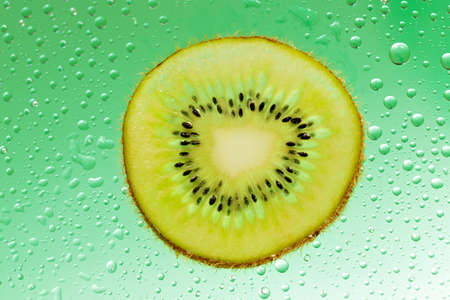 Slice of kiwi with drop on green background photo