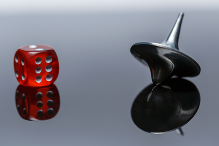 Whirligig and dice with reflection on a dark background