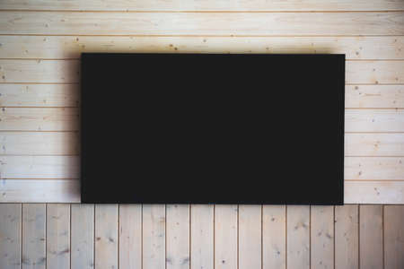 Big turned off TV on wooden wall