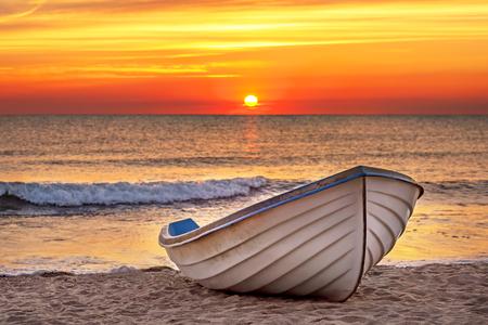 bateau de pêche: Bateau sur la plage au moment du lever du soleil.
