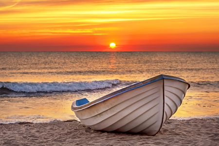 Boat on the beach at sunrise time.