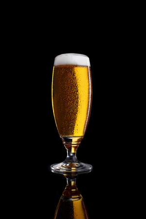 Glass of light beer isolated on a black background.