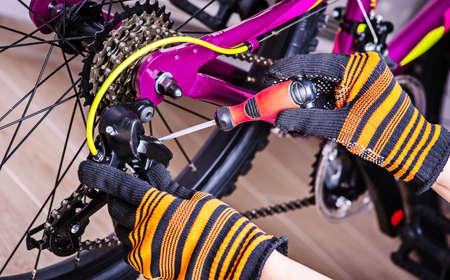 Mechanic serviceman repairman installing assembling or adjusting bicycle gear.