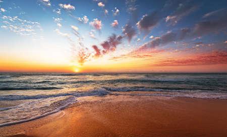 Colorful ocean beach sunrise with deep blue sky .