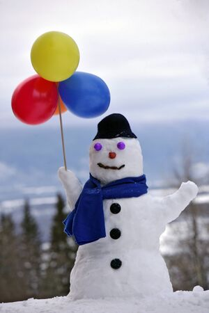 Snowman with hat and scarf holding balloons Stock Photo