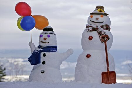 Two smiling Snowmen decorated with scarves,hats and balloons, sky background